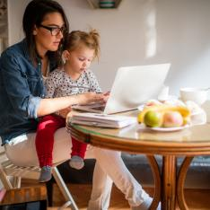 Woman attempts to work on computer, while holding toddler on her lap