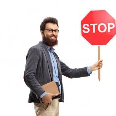 "Teacher, holding books and a ""Stop"" traffic sign"