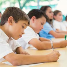 Primary pupils sit at their desks and take a test