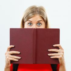 A woman gazes, wide-eyed, over the cover of a book