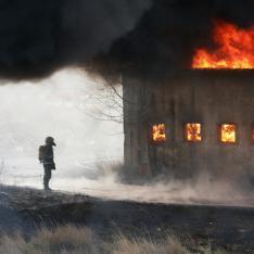 Man, standing next to burning building