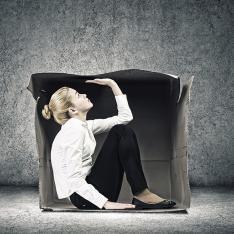 Woman, squeezed into cardboard box
