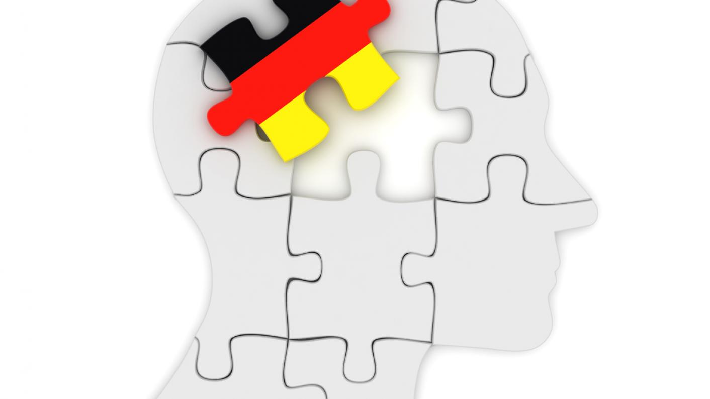 Man's head as jigsaw puzzle, with one piece in colours of German flag
