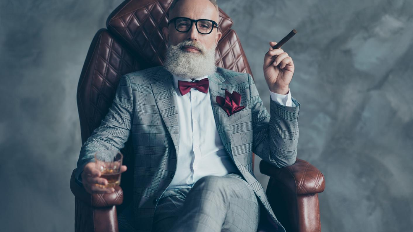 Besuited, bearded, bespectacled man, in armchair