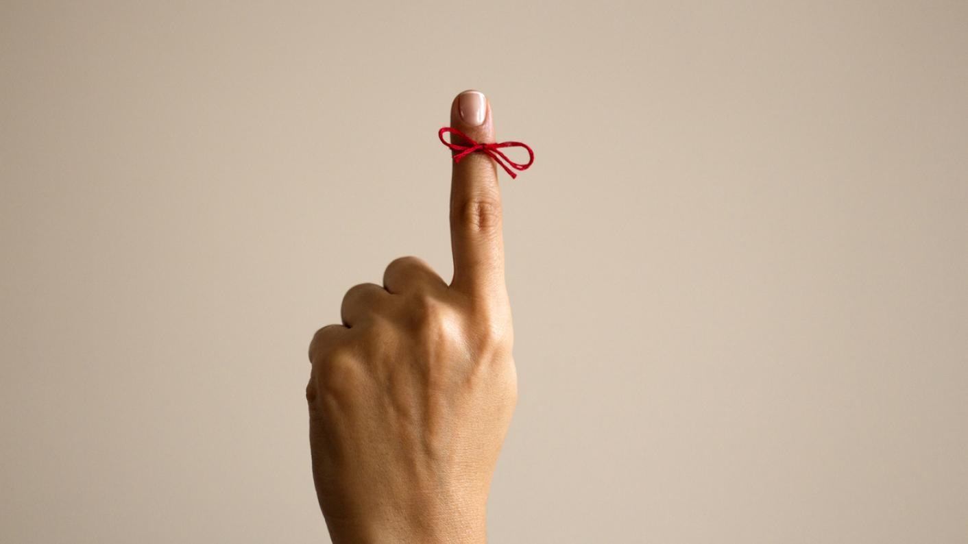 Red string knotted around finger