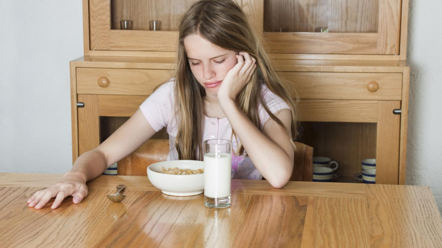 Eating disorders: Sad-looking girl with food and drink
