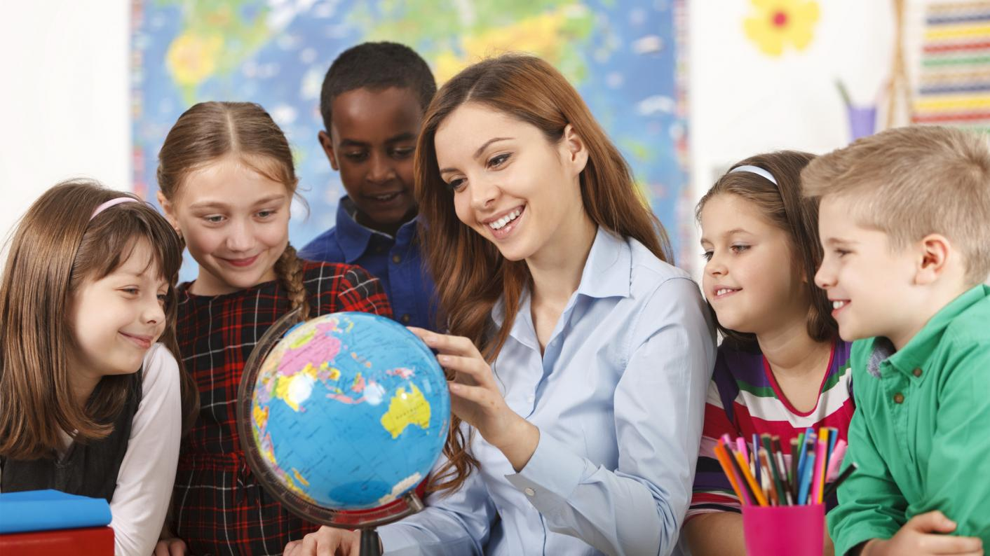 Teachers looking at globe with pupils