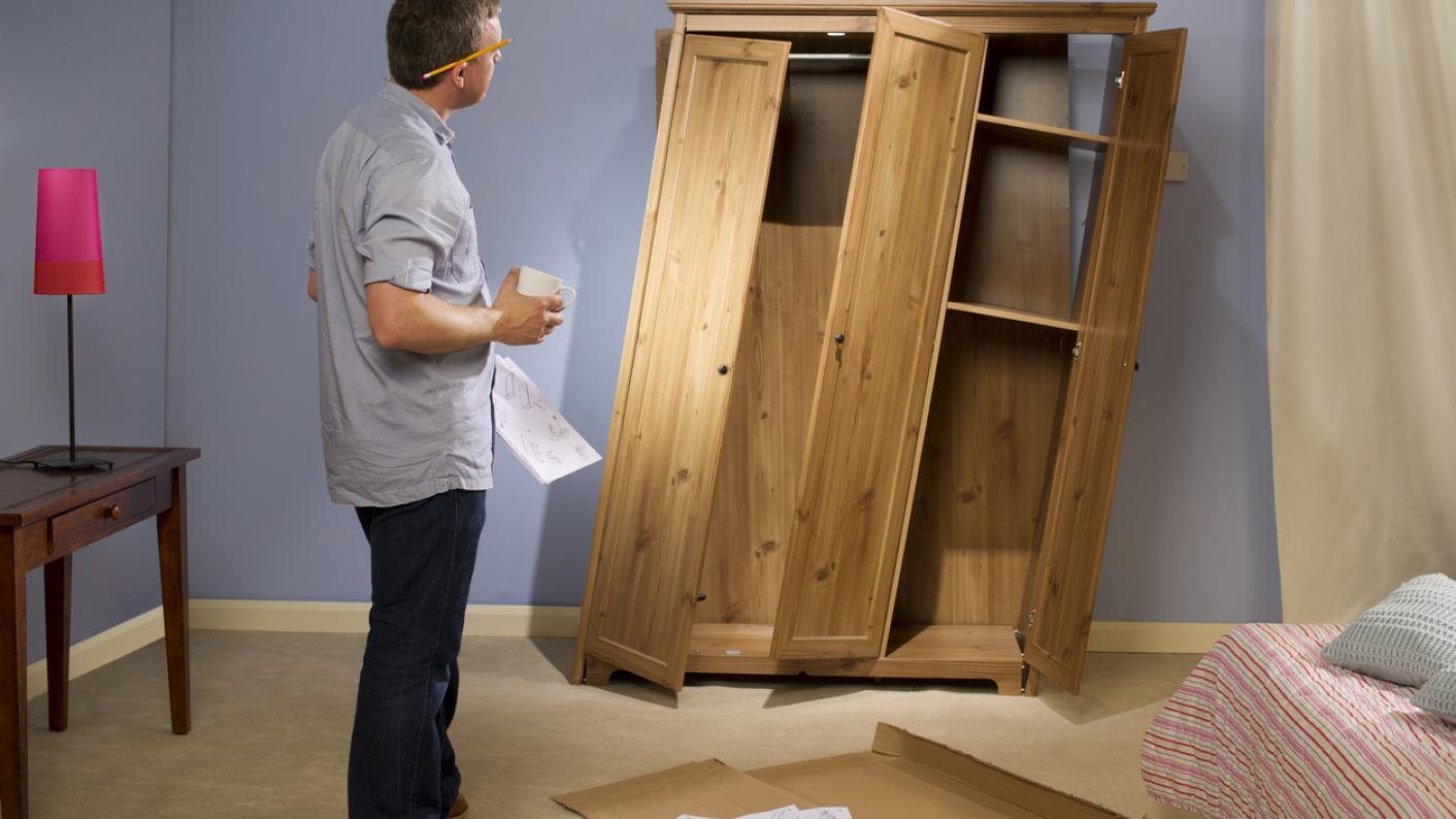 Man gazing at badly assembled wardrobe