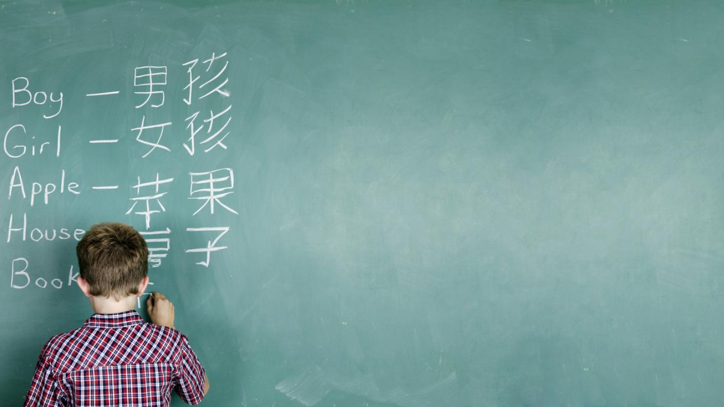 Boy at blackboard, learning Mandarin