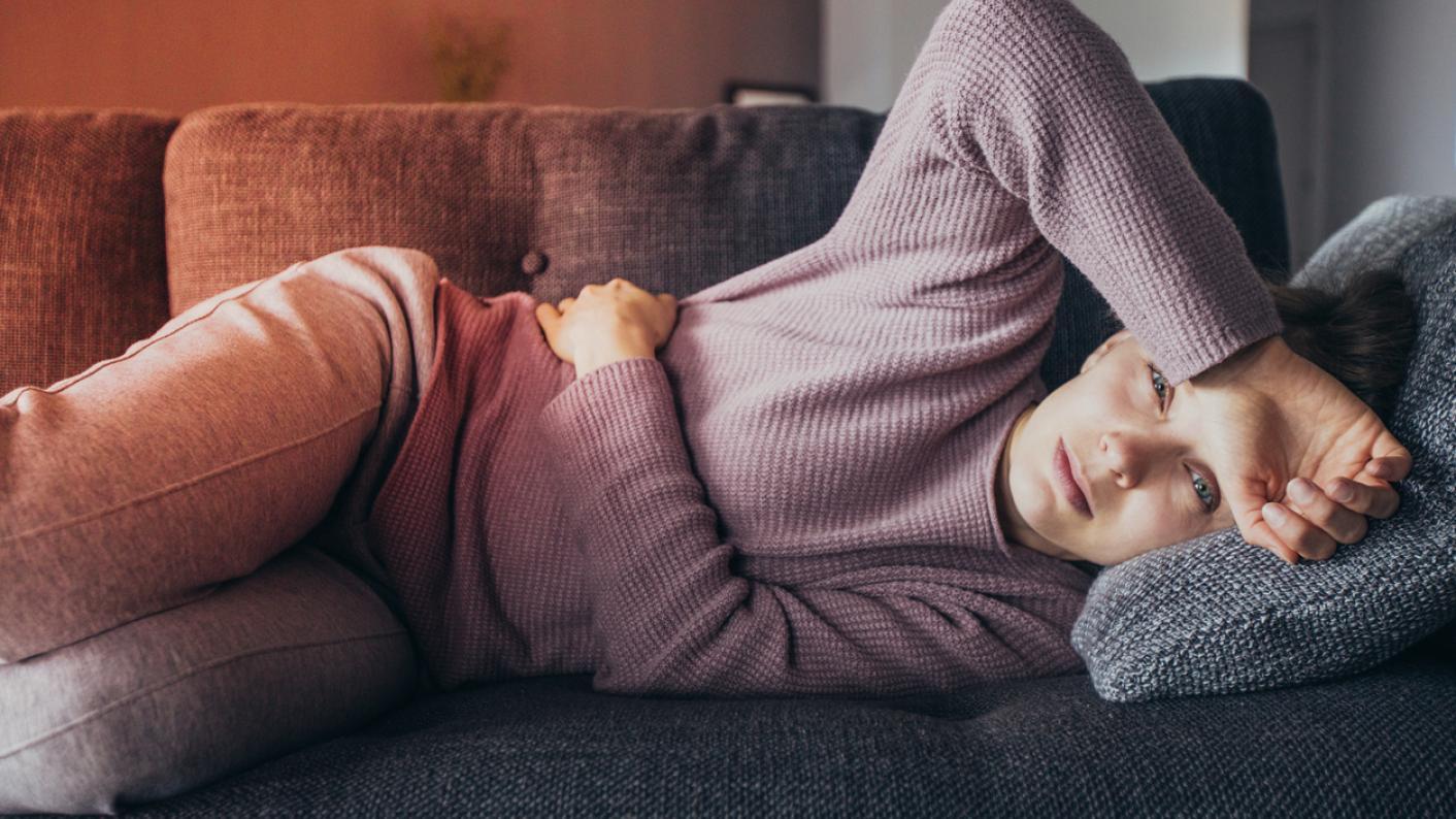 Woman, lying on sofa, in pain