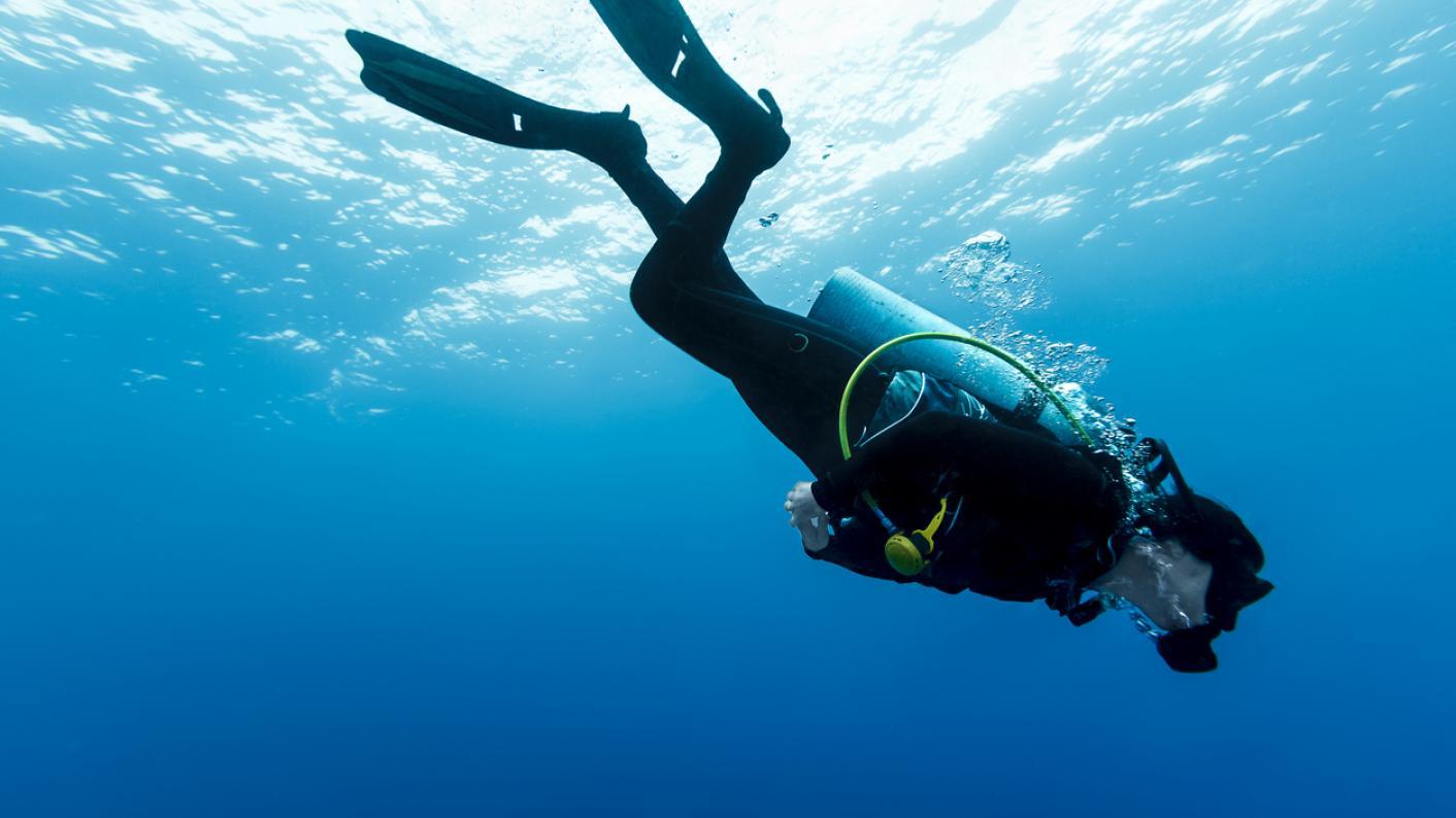 Scuba diver descends into sea