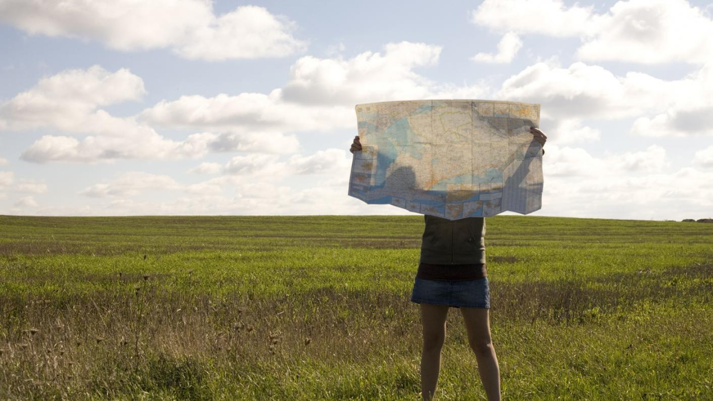 Person in countryside, hidden behind large map