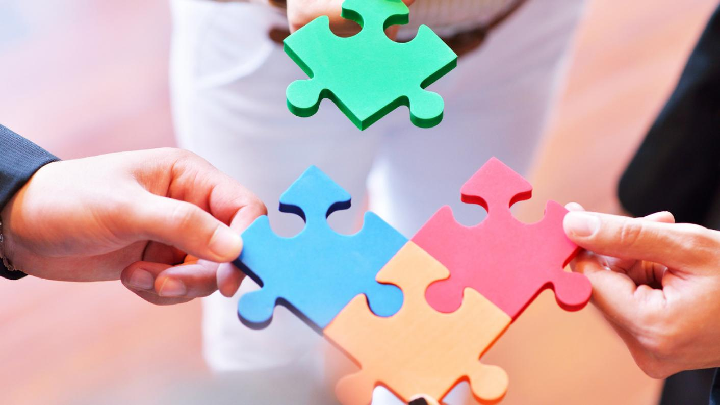 Four pieces of a jigsaw puzzle, being joined together