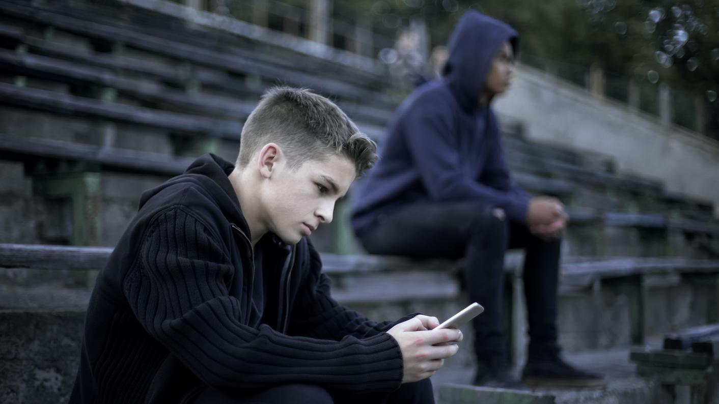 Boy gambling on his phone at school