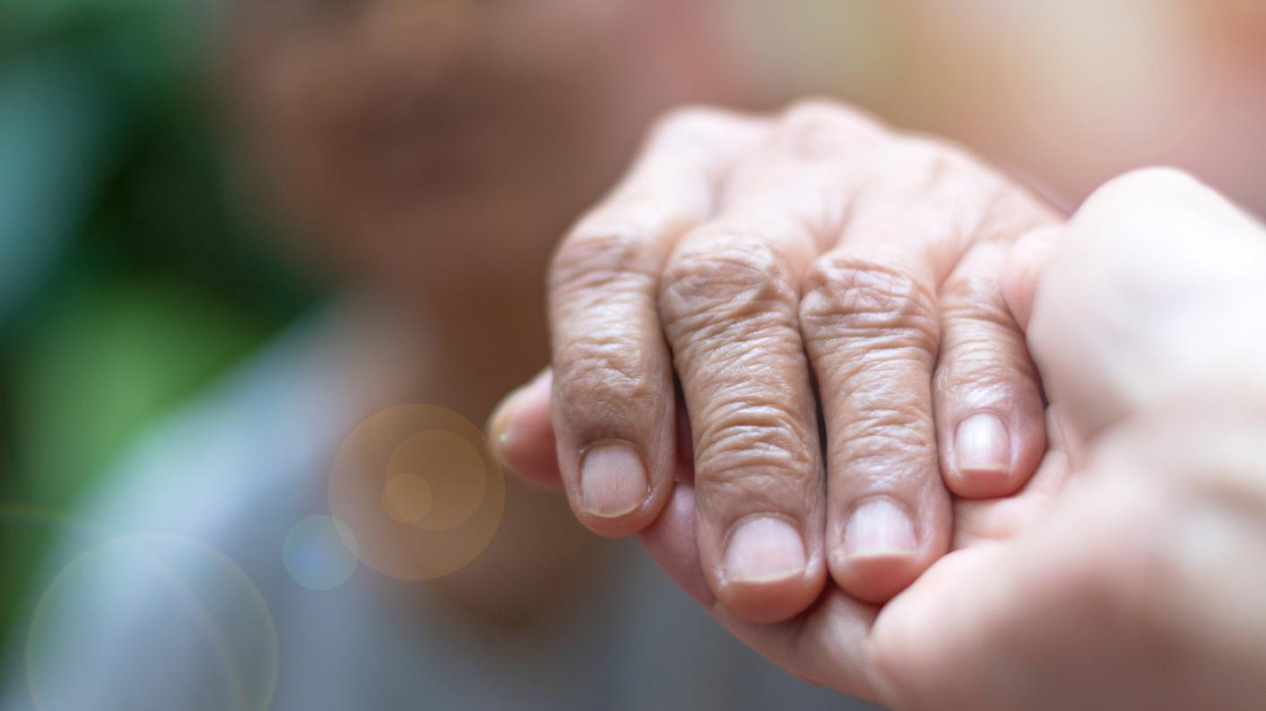 Holding hands: a young hand and an elderly hand
