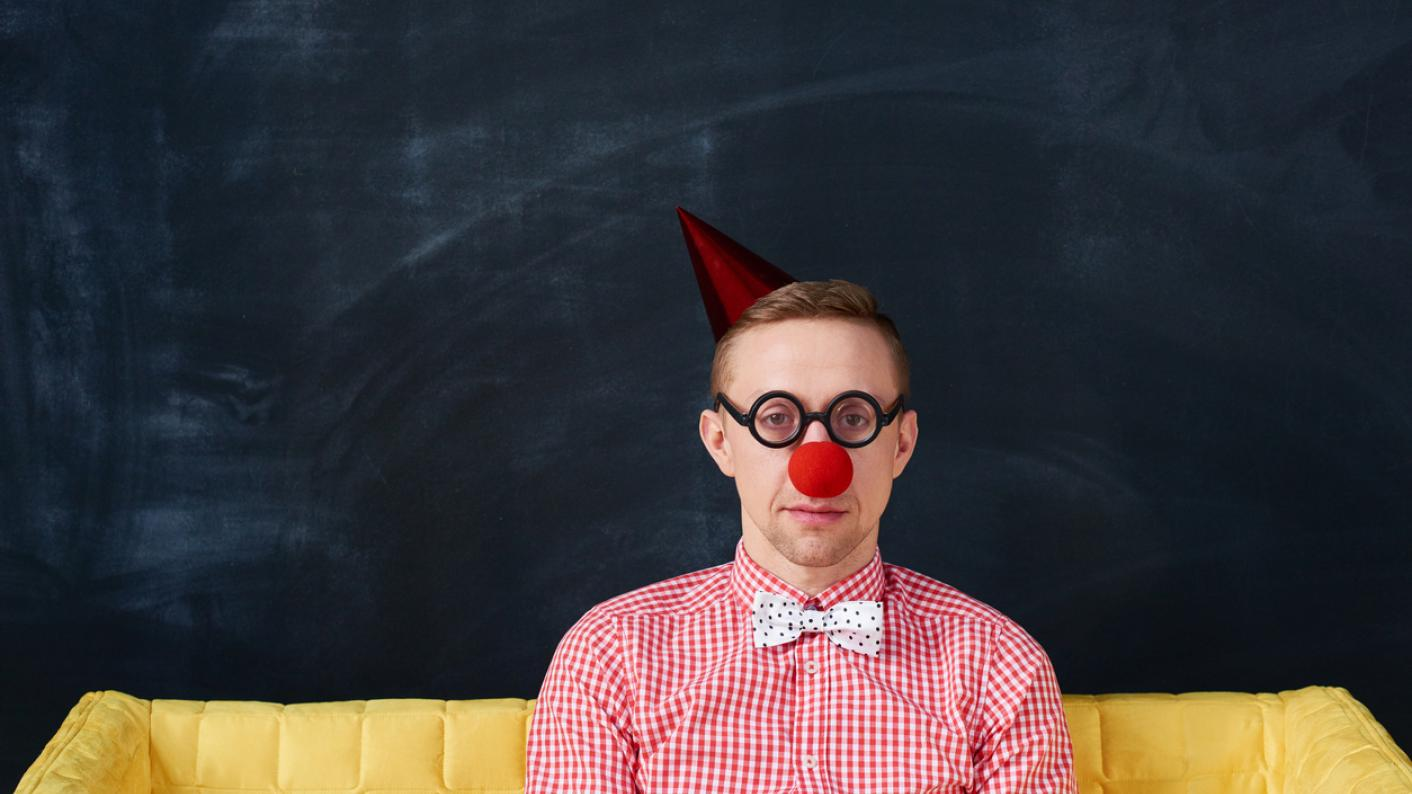 Man in clown outfit, looking unimpressed