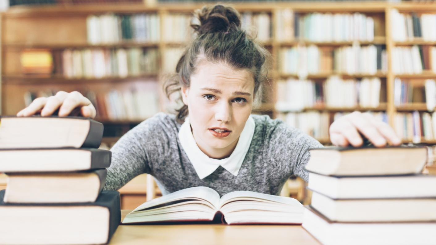 Girl, surrounded by books, looking fed up