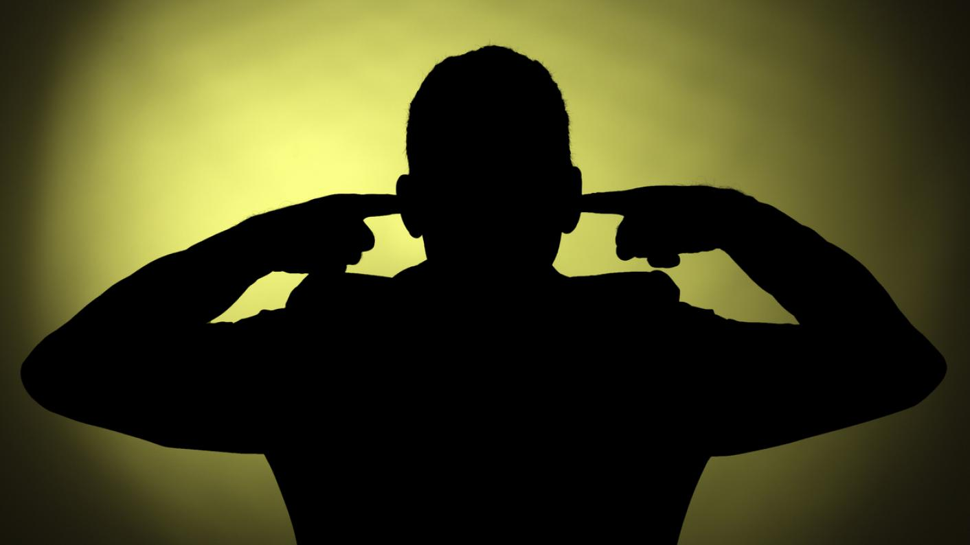 Silhouette of man, with his fingers in his ears