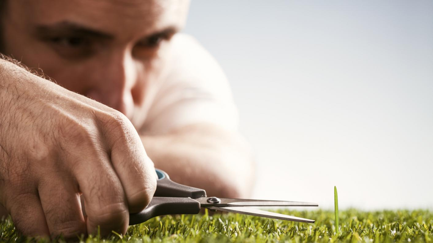 Man with scissors snips at one blade of grass that's taller than the others