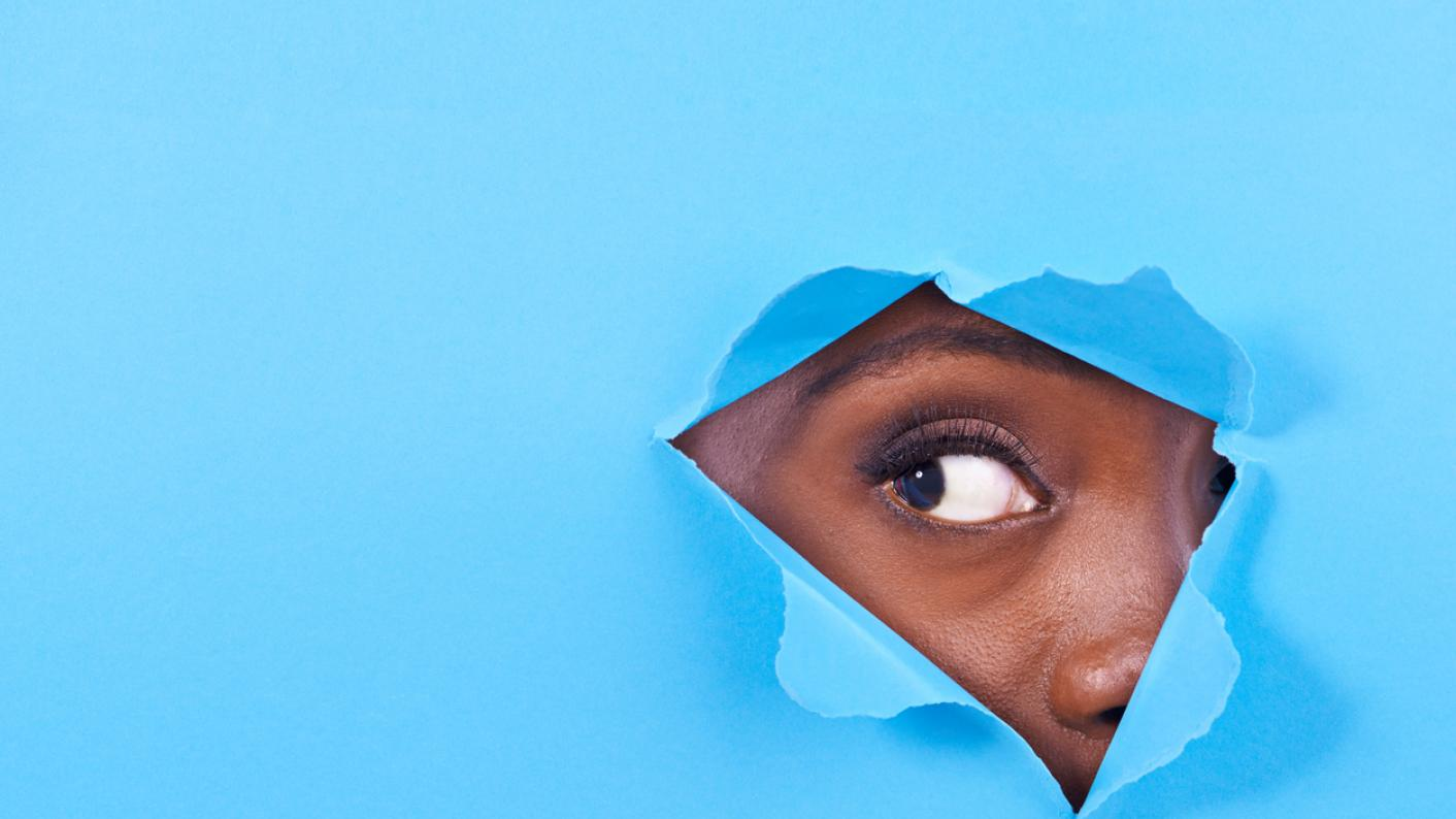 Woman looks out, through tear in blue background