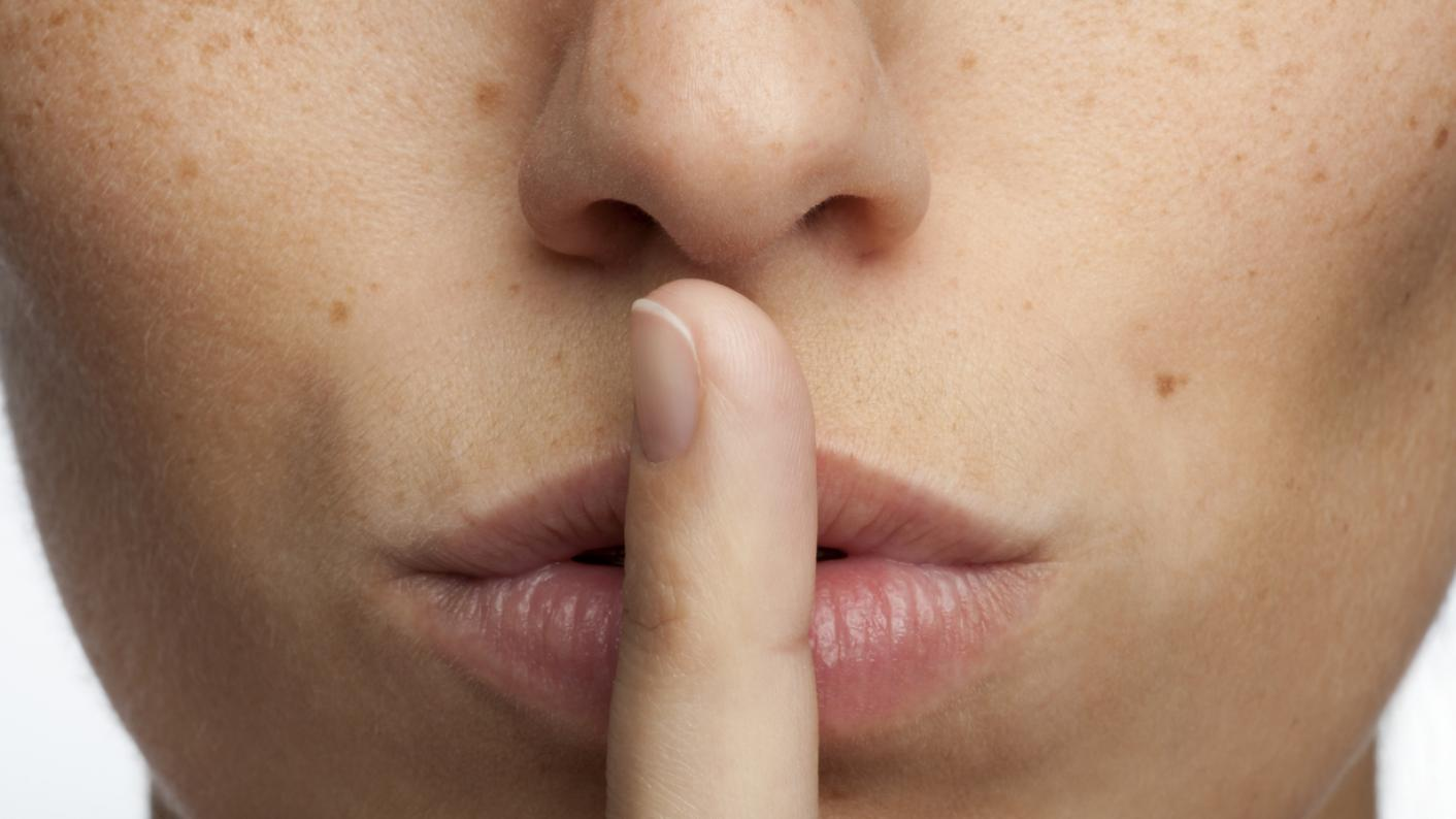 Woman with finger on her lips, indicating quiet