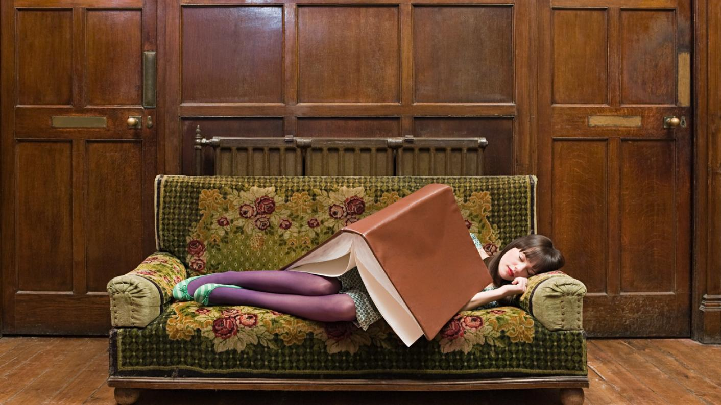 Woman, sleeping on sofa under giant book
