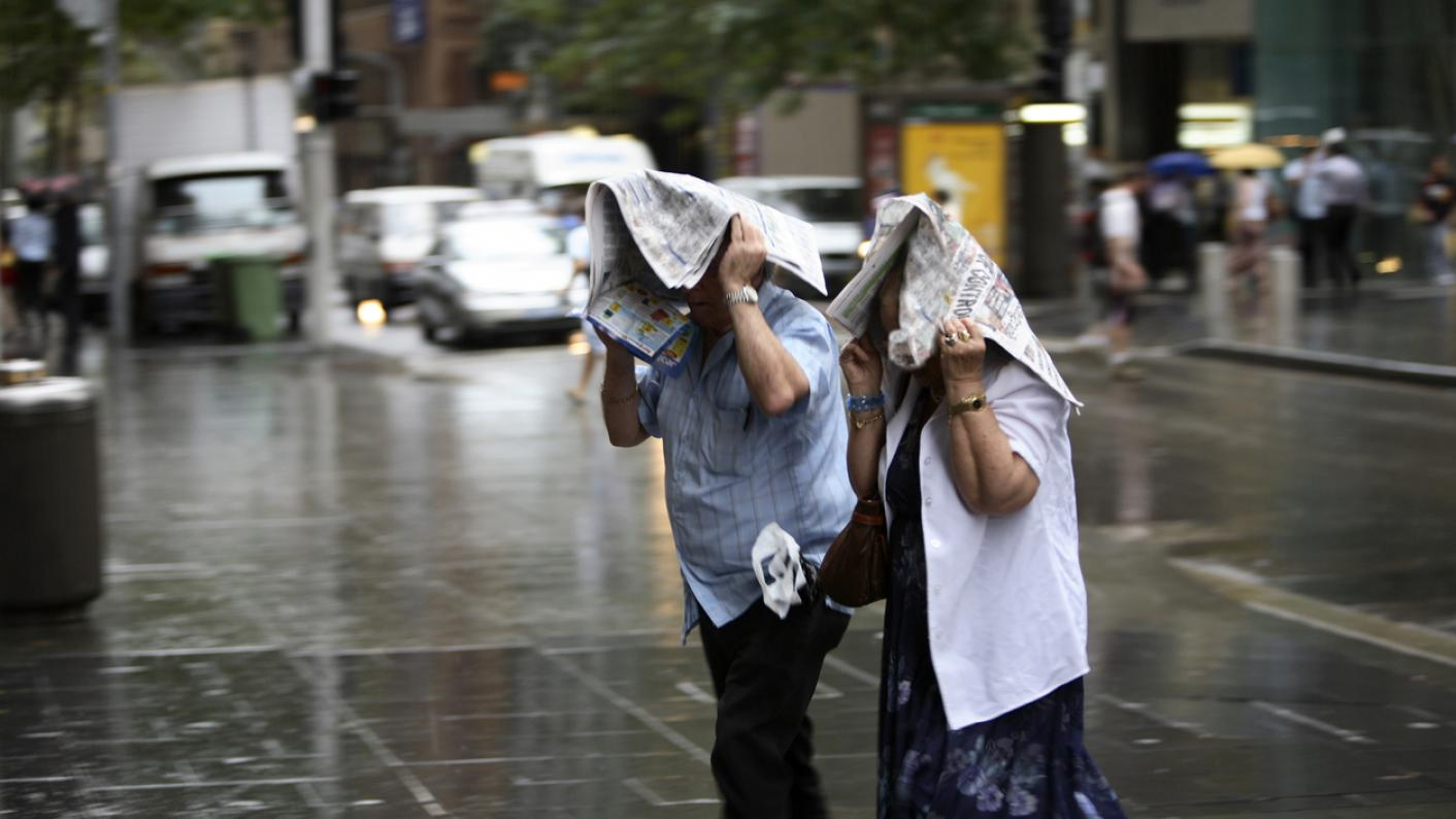 People using paper to shield themselves from the rain