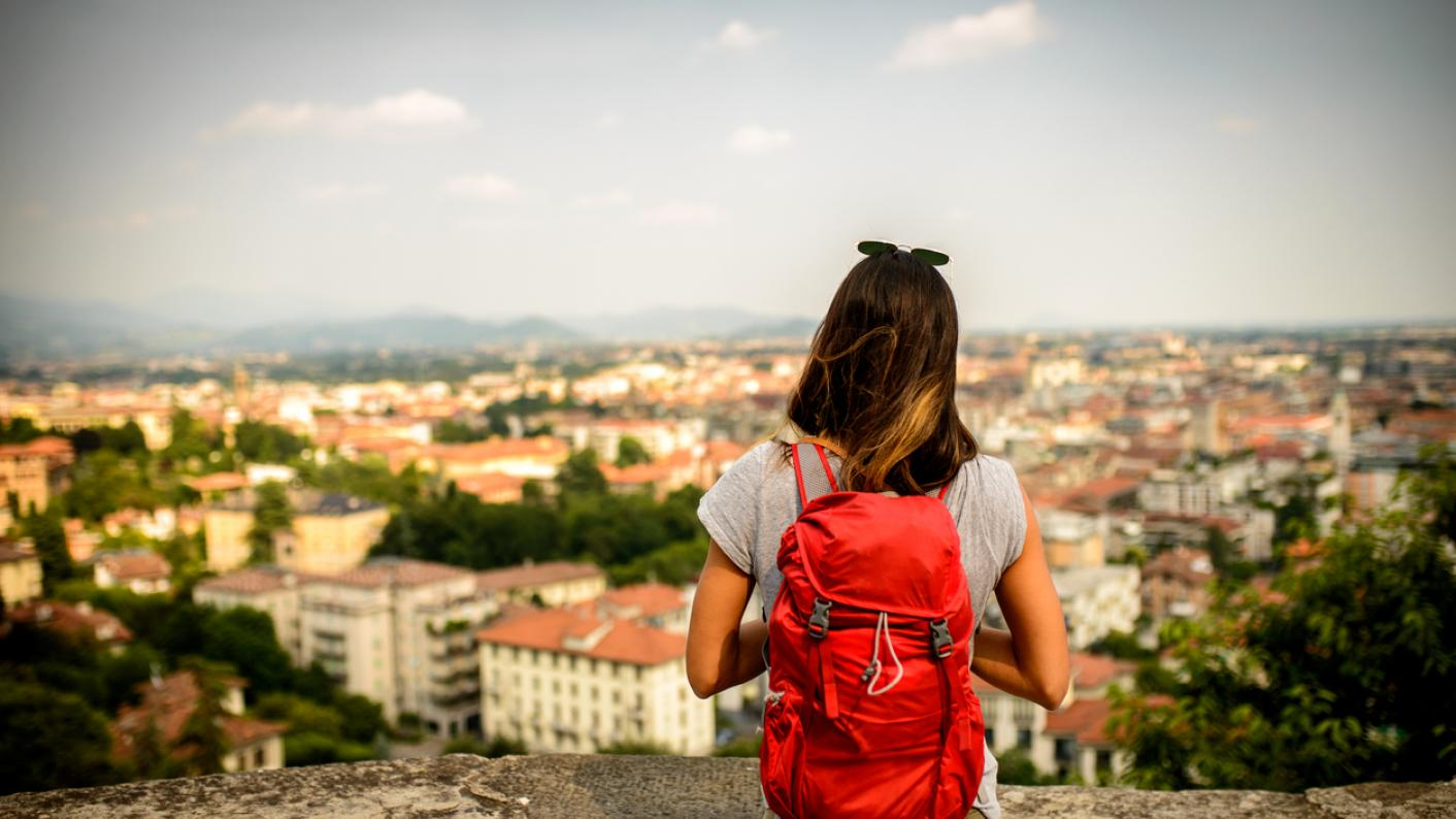 Schoolgirl gazes out, over view of Bergamo, in Northern Italy