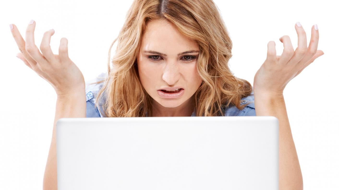Woman looks at computer in confusion