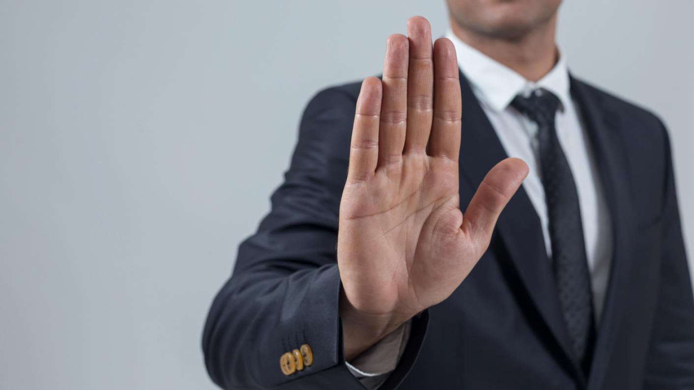 Man in suit, holding up hand of rejection