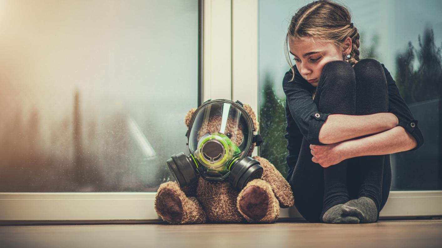 Sad girl sits next to teddy bear in gas mask