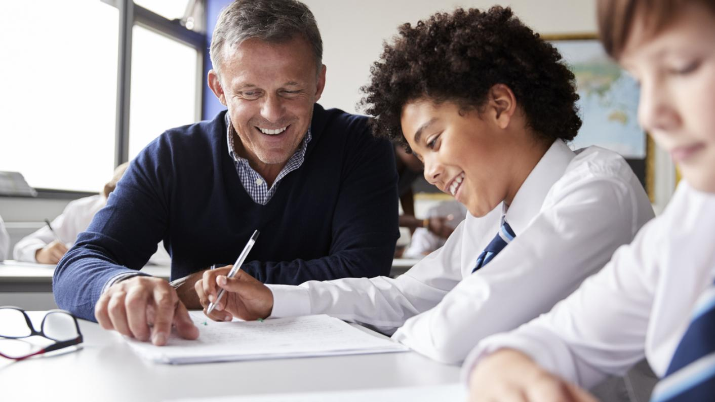 Teacher sitting at desk, helping pupil with work