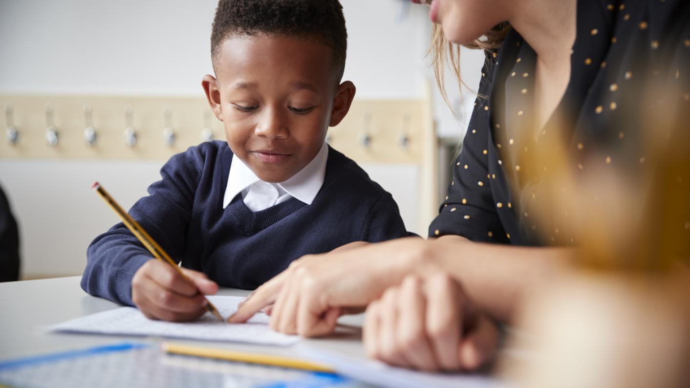Teacher helping pupil at school