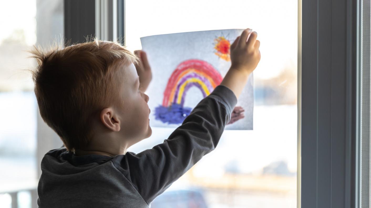 child sticking photo on window