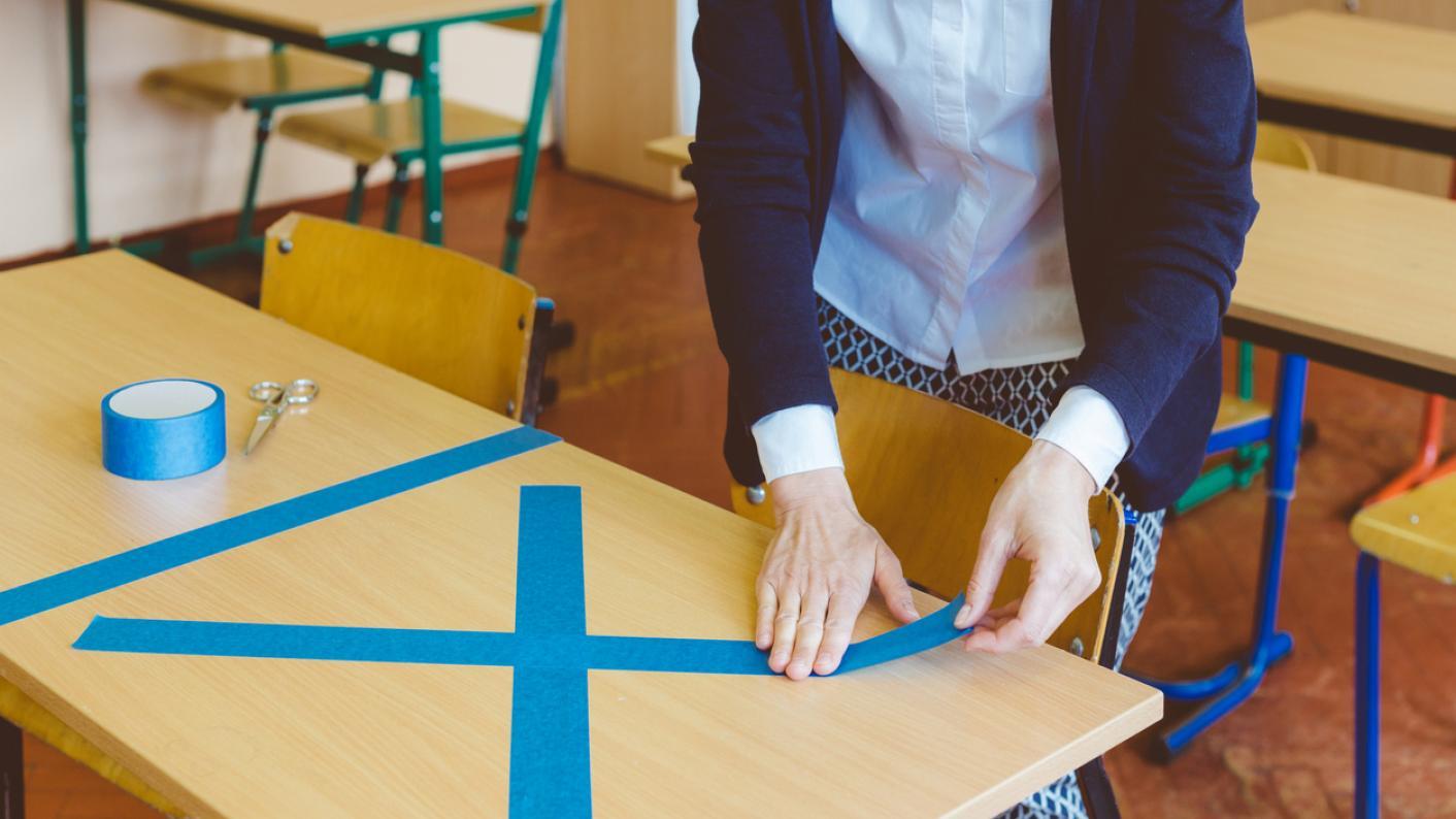 Teacher cordoning off classroom desk