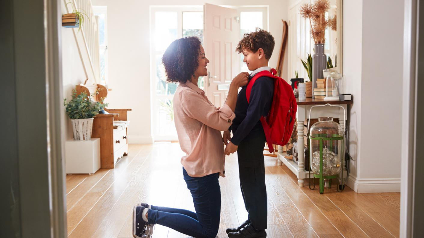 Mother adjusts son's uniform for first day at new school