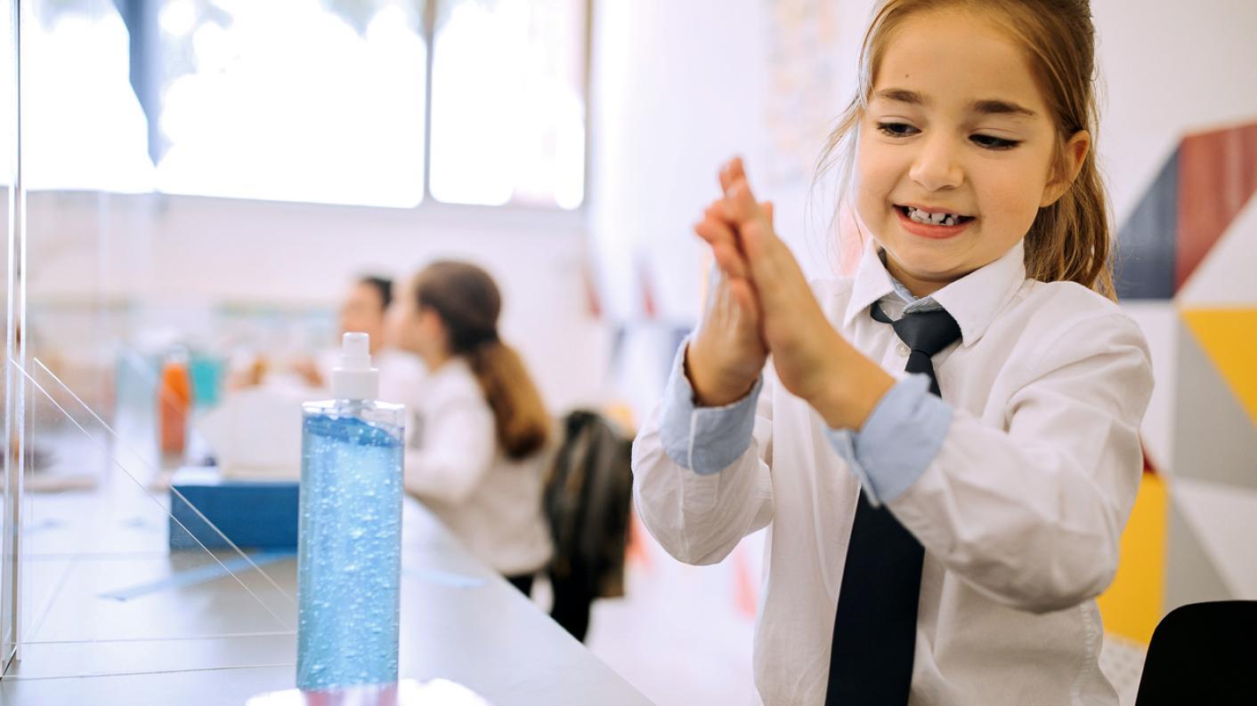 Schoolgirl uses hand sanitiser before lunch