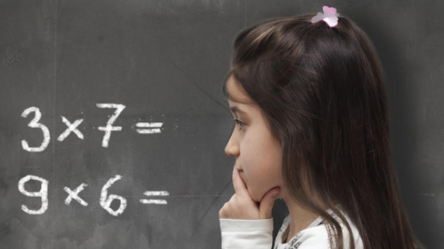 Young pupil standing at a chalkboard doing multiplication questions