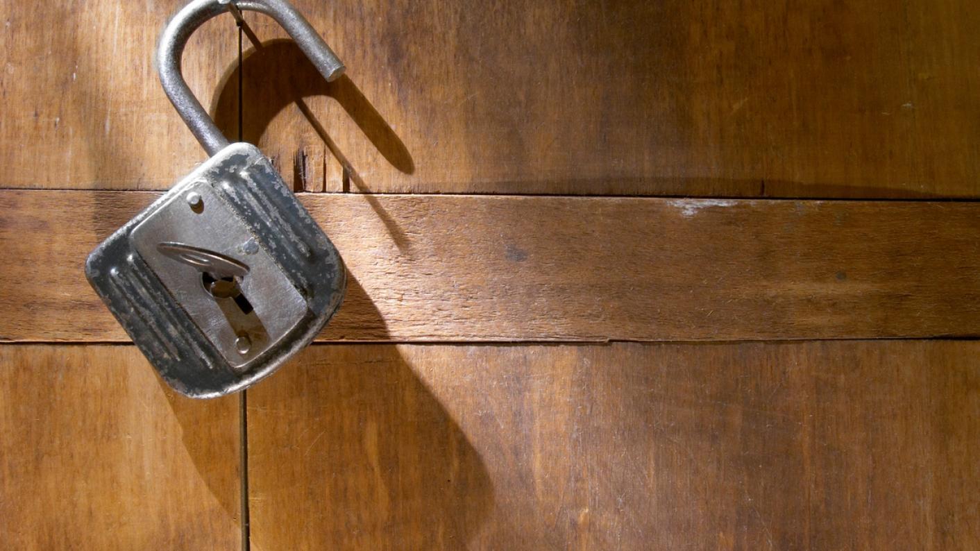 Open padlock, against wooden background