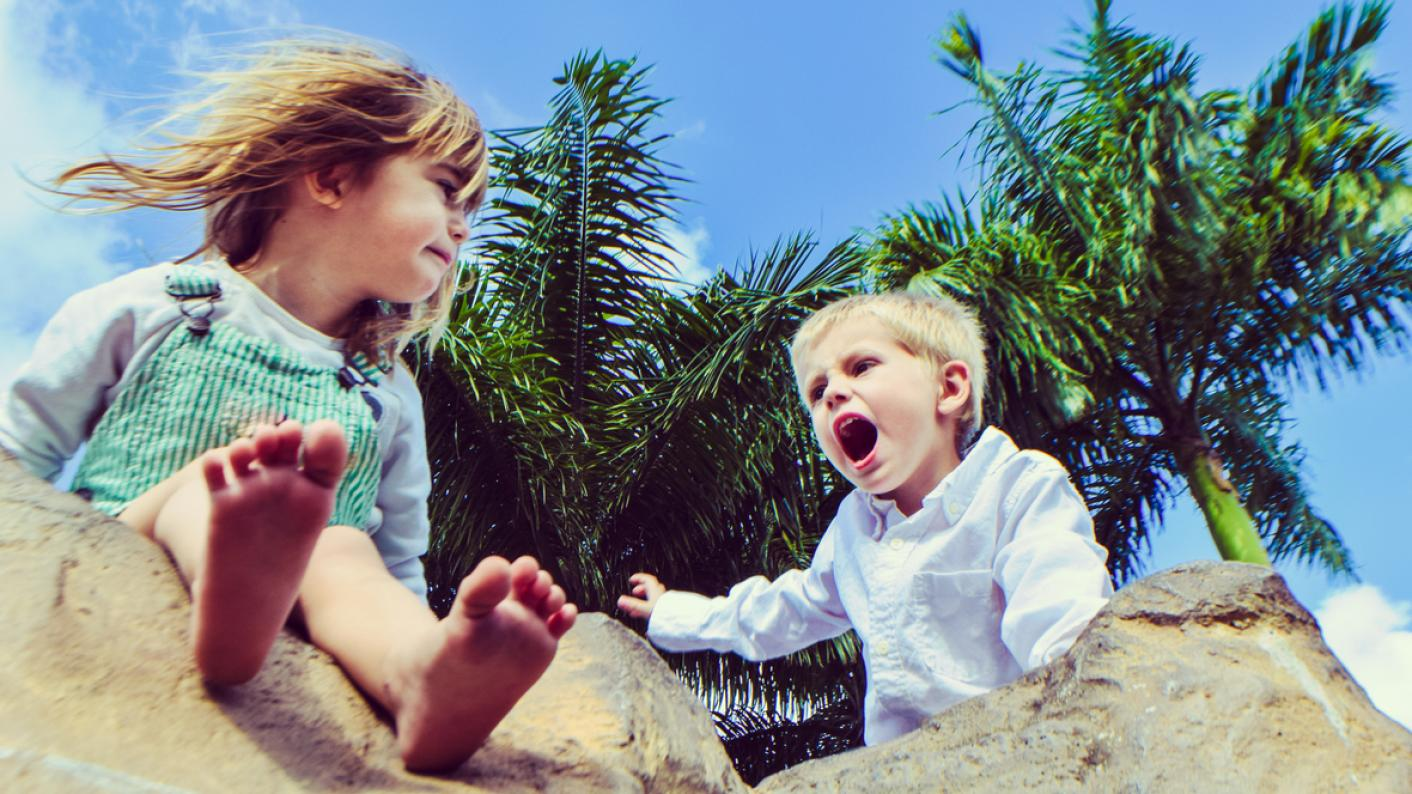 Toddler boy shouts at toddler girl in sandpit