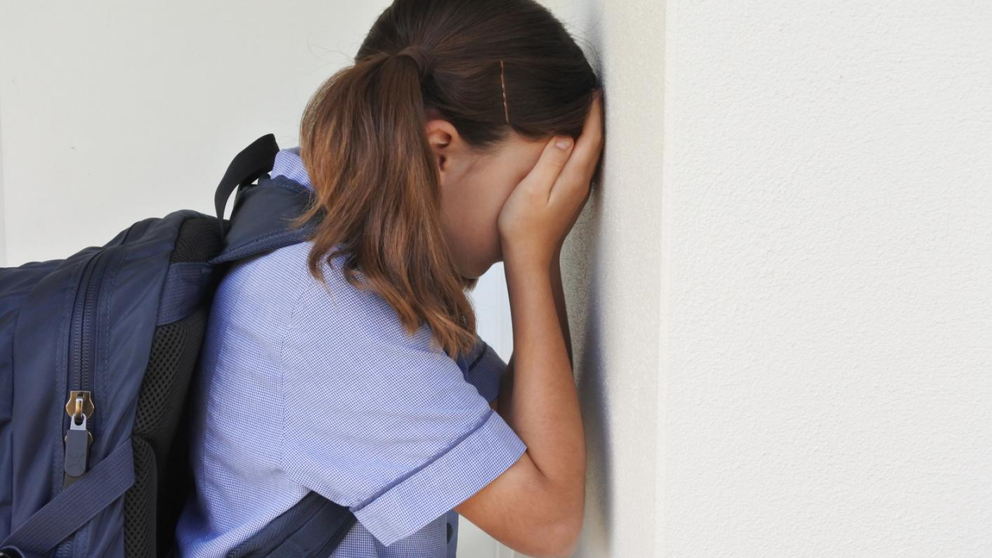 Schoolgirl, leaning against a wall and crying