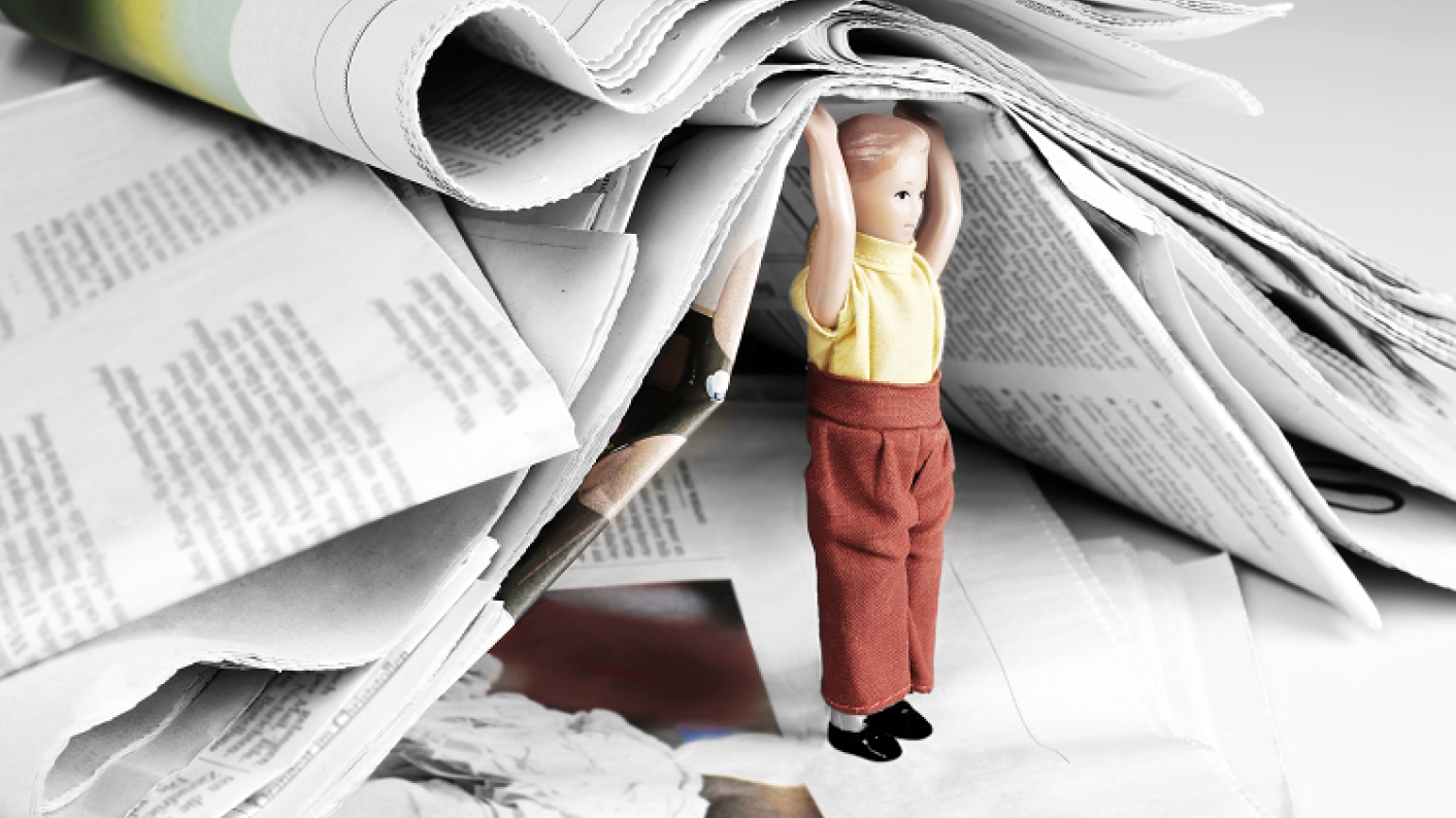 A Student Holding Up Newspapers Looking At Non-fiction Text Resources