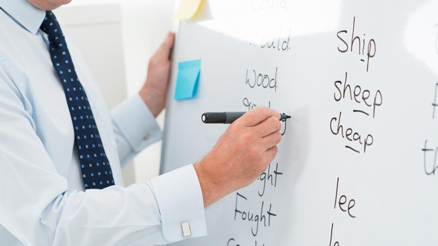 Image Of Teacher Writing Spellings On A Whiteboard For KS1 & KS2 Pupils