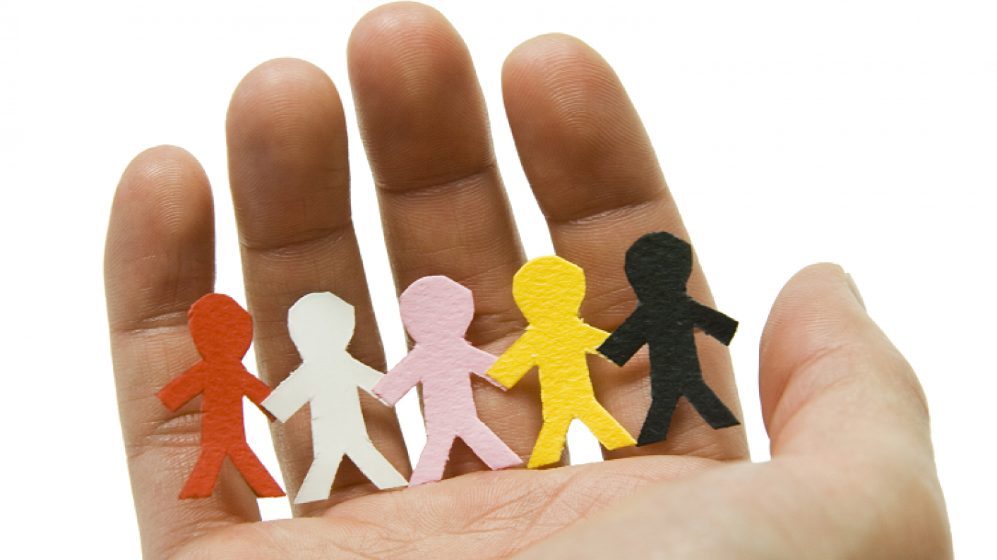 Hand Holding Row Of Paper People To Illustrate Safeguarding In Schools